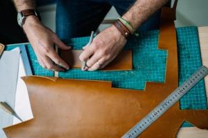 Mand der arbejder med læder til møbelpolstring